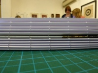 Al the signatures with holes in their spines, ready for binding.